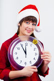 Blue-eyed beautiful girl in santa hat with clock Stock Photo