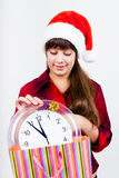 Blue-eyed beautiful girl in santa hat with clock Royalty Free Stock Images