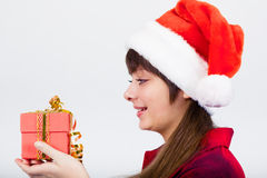 Blue-eyed beautiful girl in santa hat with presents Royalty Free Stock Photo
