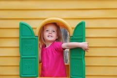Blue-eyed blond baby toddler happy. Happy blond blue-eyed baby toddler in the toy house royalty free stock photo