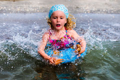 Blue eyed blond little girl playing in the water. Portrait of a blue eyed blond baby girl on the beach nice dressed with a blue swim ring in the summer holiday Royalty Free Stock Images