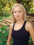Blue-eyed blonde. Serious white-headed girl in the black opened t-shirt outdoors Stock Photography