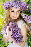 Blue-eyed blonde girl with wreath from lilac flowers. Portrait of beautiful blue-eyed teenager girl with wreath from lilac flowers Royalty Free Stock Photos