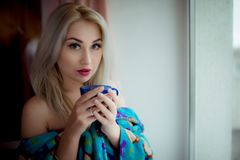 Blue-eyed blonde in a home dressing-gown near a window with a blue cup. This shot was made in bedroom near window in October,2016 in Kiev, Ukraine stock photography