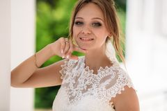 Blue-eyed blonde in a lace embroidered dress posing in the photo. A girl looks at the camera and smiles with her hand on royalty free stock photography