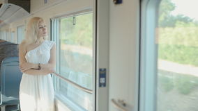 Blue-eyed blonde standing by the window of the train stock video footage
