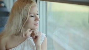 Blue-eyed blonde standing by the window of the train stock footage