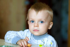Blue-eyed boy. A little boy is at a table and holds a thin captain in a hand Stock Photography