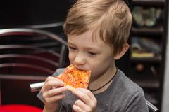 The boy eats a very tasty pizza with great pleasure. stock images