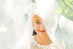 Blue-eyed bride smiles being hidden under a veil Royalty Free Stock Images