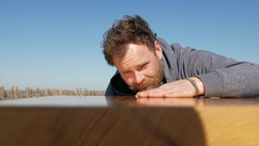 Carpenter with a beard and mustache against a blue sky touches the surface of the table, made by him by hand. handmade. A blue-eyed carpenter with a beard and stock video footage