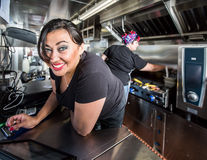 Blue Eyed Cashier On Food Truck. Dark haired smiling cashier with blue eyes on food truck stock photo