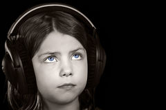 Blue Eyed Child with Headphones against Black Stock Photo