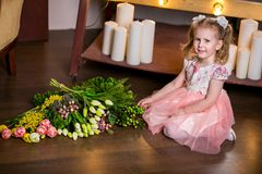 Blue-eyed cute girl in a pink dress sits on the floor next to a bouquet of tulips, mimosa, berries and greenery royalty free stock images