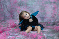 Blue Eyed Fairy. Adorable little girl is wearing a fairy costume and sitting in a room filled with pink and grey. Her eyes are vivid blue and match her wings and royalty free stock images