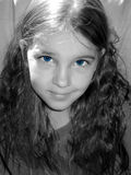 Blue-eyed girl. Beautiful child with bright blue eyes.  Black and white image with blue coloration Stock Image