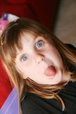 Blue eyed girl 2. Young girl with blue eyes and her tongue out royalty free stock photos