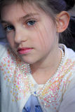 Blue eyed girl. A very cute little girly girl with blue eyes and dark hair wearing pearls, beads and makeup. Shallow depth of field Royalty Free Stock Images