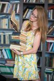 Blue-eyed girl with red hair in the library Royalty Free Stock Photography