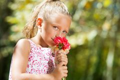 Blue eyed girl smelling flower outdoors. Stock Photography