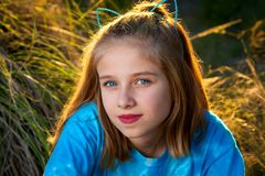 Blue Eyed Girl Smirks For the Camera. Beautiful blue-eyed girl smirks knowingly at the camera. She is wearing a bright blue shirt and a headband with cat ears stock photo