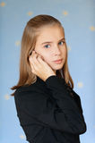 Blue-eyed girl-teenager talking on. Beautiful blue-eyed girl-teenager in business suit talking on cell phone, on blue background Stock Photo