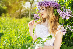 Blue-eyed girl with wreath from flowers in green park. Portrait of beautiful blue-eyed teenager girl with wreath from lilac flowers Royalty Free Stock Photo