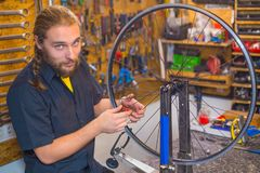 Blue eyed guy repairing bicycle in the workshop stock photo
