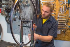 Blue eyed guy repairing bicycle in the workshop stock photos
