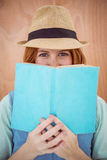 Blue eyed hipster woman looking over the top of a book Royalty Free Stock Photos