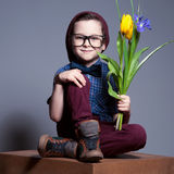 A blue - eyed kid with glasses.A boy sits with a smile on face. Young boy  wearing a glasses. He sits with a smile on face is wearing plaid shirt and burgundy Stock Image