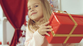 Blue-eyed little blonde girl is delighted from her New Year`s gift Stock Photo