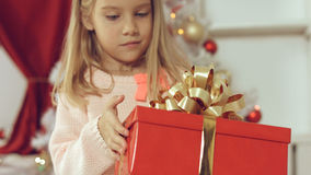 Blue-eyed little blonde girl is delighted from her New Year`s gift Royalty Free Stock Images