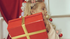 Blue-eyed little blonde girl is delighted from her New Year`s gift Stock Photography