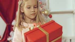 Blue-eyed little blonde girl is delighted from her New Year`s gift Royalty Free Stock Image