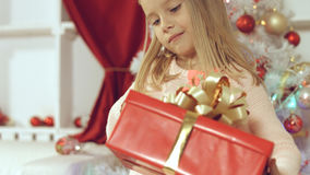 Blue-eyed little blonde girl is delighted from her New Year`s gift Royalty Free Stock Photography