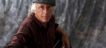 Blue eyed man with glasses and grey hair wearing cap Royalty Free Stock Photo
