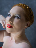 Blue-eyed red-haired woman. With bright red lipstick on a grey background Royalty Free Stock Photos