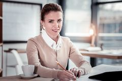 Blue-eyed sales manager feeling busy while writing important business letter. Business letter. Amicable blue-eyed sales manager feeling busy while writing royalty free stock photo