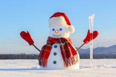 The blue eyed smiling snowman in red hat, gloves and plaid scarf holds the icicle in hand. Joyful cold winter morning. Field in snow stock image