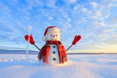 Blue eyed snowman. Sunrise enlightens the sky and clouds by warm colors. Reflecting on the snow. Mountains landscape. stock photography