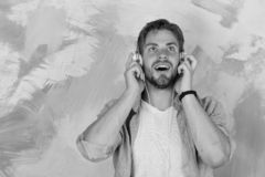 Blue eyed stylish hipster with smartphone. Cheerful teenage dj listening songs via earphones. American handsome bearded. Guy with headphones. Musical lifestyle royalty free stock photo