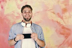 Blue eyed stylish hipster with smartphone. Musical lifestyle. Cheerful teenage dj listening songs via earphones. European guy have fun time. American handsome stock images
