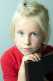 Blue eyed thoughtful young girl. Portrait of beautiful young girl (six year old), blue eyed, staring at the camera thoughtfully Stock Image