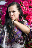 Blue-eyed woman with the african pigtails. Intent look of beautiful blue - eyed woman with the african pigtails on a background blooming azalea stock photography