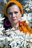 Blue-eyed woman among of magnolia Stock Image