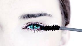 Blue eyed woman making up with mascara Royalty Free Stock Photo