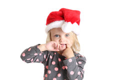 Blue eyed young girl with finger in mouth in santa hat Stock Photography