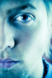 Blue eyes. Closeup of a 20 year old man's face with with emphasis on one eye and the left side of his face.  Digitally processed color Royalty Free Stock Photos