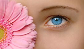 Blue eyes. Young girl with blue eyes and flower in front of her head, focus on eye Stock Photography